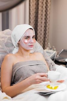 미용실의 뷰티 살롱에서 어린 소녀가 침대에 누워 얼굴에 마스크를 쓰고 눈 밑에 패치를 씌 웁니다.