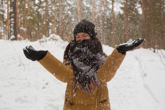 검은 모자와 갈색 재킷을 입은 어린 소녀가 겨울 숲에서 눈을 재생합니다.