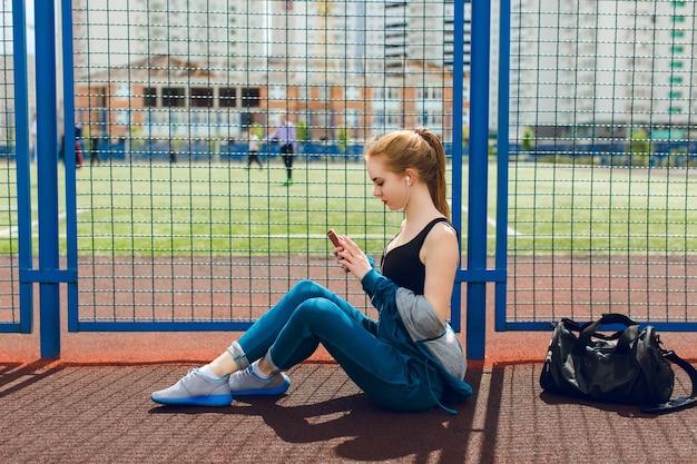 黒のトップと青いスポーツスーツの少女は、スタジアムのフェンスの近くに座っています。彼女はヘッドフォンで音楽を聴いています。