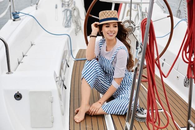 Молодая девушка в синем полосатом комбинезоне и соломенной шляпе сидит на палубе яхты в лазурном море