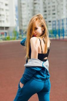青いトラックスーツと黒いトップシャツの少女がスタジアムに立っています。彼女は髪が長く、体型が良い。彼女はカメラに微笑んでいます。