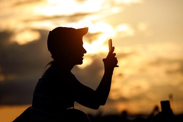 帽子をかぶった少女がスマートフォンを使って写真を撮ります。夕焼け空を背景に黒いシルエット。