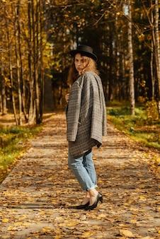 Молодая девушка в пальто и шляпе гуляет по осеннему парку