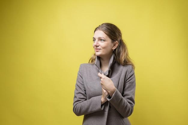 コートを着た若い女の子が黄色の背景のスタジオでポーズをとる。