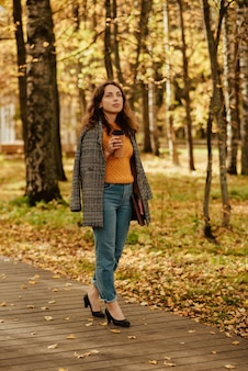 Молодая девушка в пальто гуляет по осеннему парку