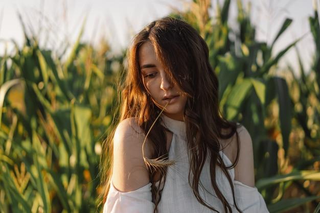 Молодая девушка на кукурузном поле с колосом пшеницы во рту. единение с природой. забота об окружающей среде