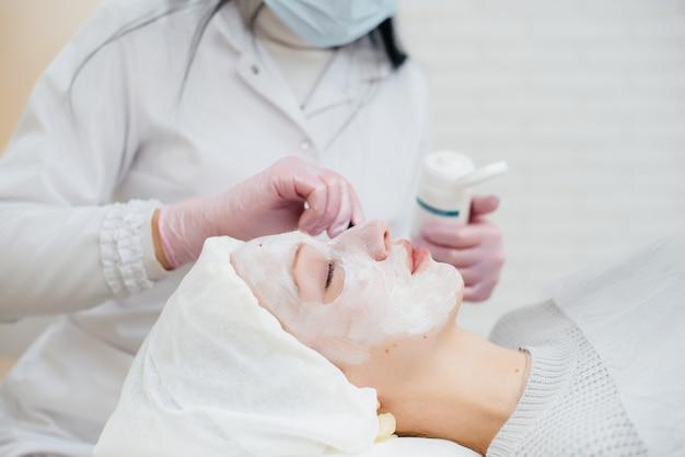 Молодая девушка в косметологическом кабинете проходит процедуру омоложения кожи лица. косметология. Premium Фотографии