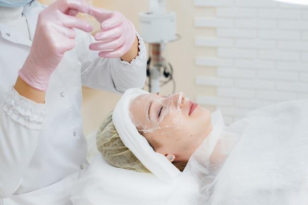 Молодая девушка в косметологическом кабинете проходит процедуру омоложения кожи лица. косметология.