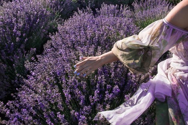 Молодая девушка в праздничном платье идет по лавандовому полю и трогает лаванду рукой.