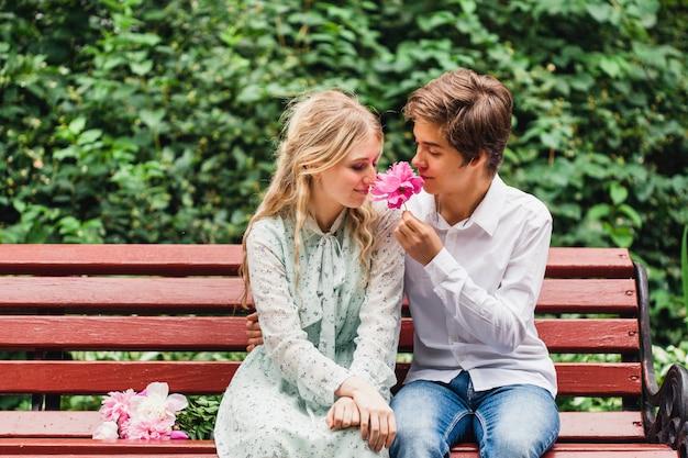 夏の軽いドレスの少女が立って、花、牡丹、花束、ギフト、デート、待っている、ベンチ、恋人、