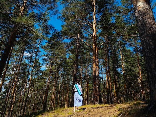 가벼운 치마를 입은 어린 소녀가 숲을 산책하고 등 뒤로 요가 매트를 들고