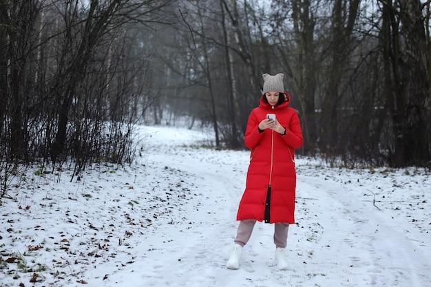 긴 빨간 다운 패딩 코트를 입은 어린 소녀가 겨울 숲에 서 있습니다.