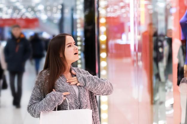 쇼핑몰에있는 어린 소녀는 가격에 놀랐습니다.
