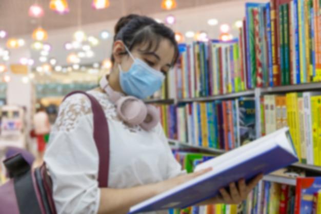 仮面をかぶった少女が店で本を選ぶ。白いブラウスの美しいブルネット。コロナウイルスパンデミック。ぼやけた。
