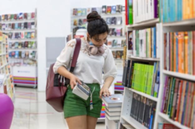 仮面をかぶった少女が店で本を選ぶ。ヘッドフォンとバックパック付きの美しいブルネット。コロナウイルスパンデミック。ぼやけた。