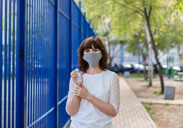 マスクをした少女が手に消毒剤を持っています。白いtシャツを着た女の子が通りに立ち、消毒剤を手にします