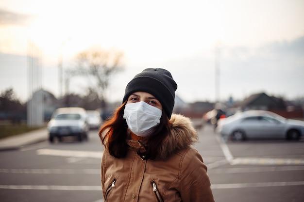 Молодая девушка в медицинской маске на улице. защита органов дыхания. коронавирус. опасная болезнь. статья о коронавирусе и его лечении. портрет женщины в черной шляпе.