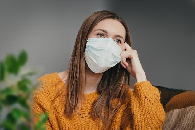 医療マスクの少女が隔離された隔離室で自宅に座って悲しい