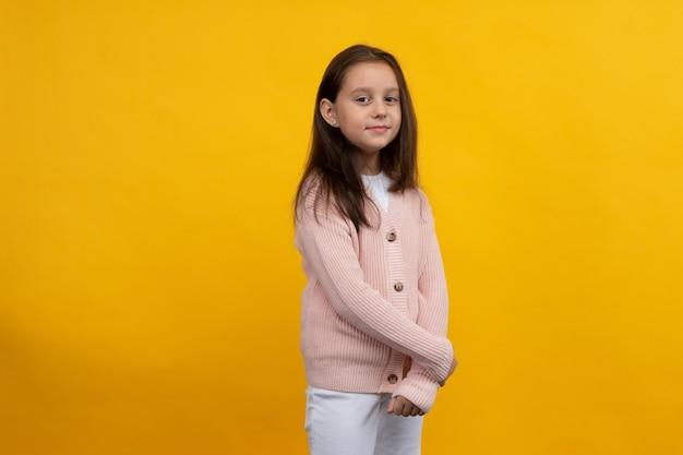ピンクのジャケットと白いジーンズの若い女の子が黄色の背景にポーズをとる