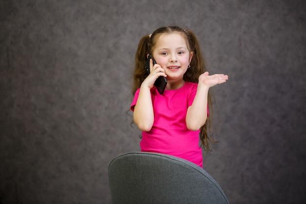 ピンクのtシャツを着た少女が電話で話します