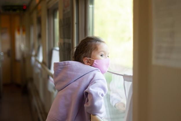 保護マスクをした少女が電車の中で旅をし、窓の外を見るパンデミック