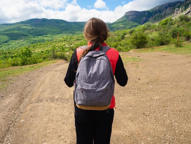緑の木々と雲と山の中で灰色のバックパックと赤いタンクトップの少女。