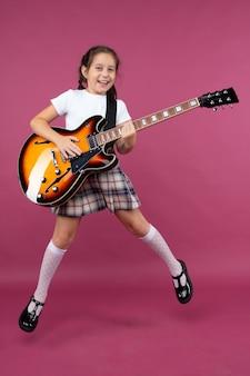 Молодая девушка в школьной форме играет на электрогитаре