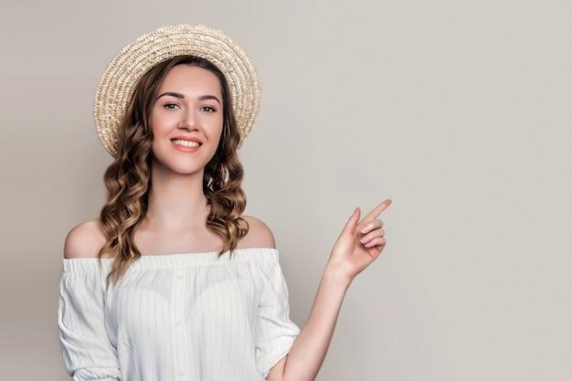 Молодая девушка в соломенной шляпе и белом винтажном платье улыбается и указывает пальцем на. девушка в летней одежде на серой стене