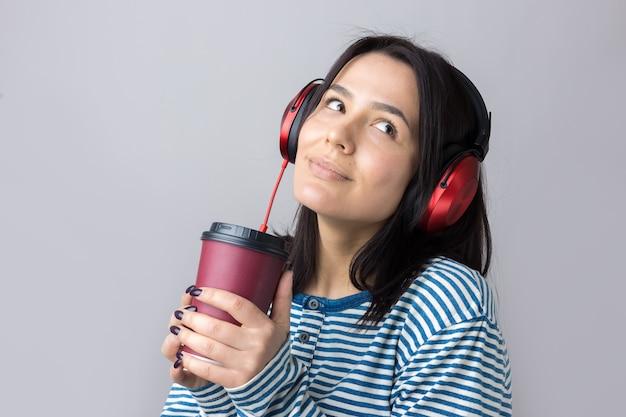 縞模様のベストを着た少女がスタジオで赤いヘッドホンで音楽を聴いて踊っています。