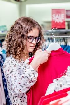 Молодая девушка в модном бутике смотрит на красное платье. покупки стильной одежды_