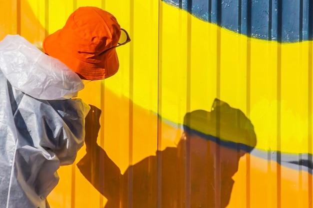 Молодая девушка в белом халате с пятнами краски красит ребристый железный забор граффити