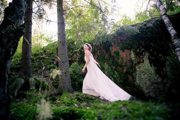 Молодая девушка в белом платье и с завязанными глазами в лесу у скалы во мхе