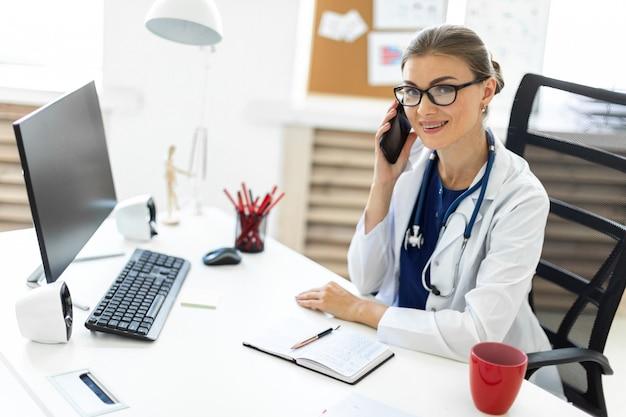 Молодая девушка в белом халате сидит за столом в кабинете и разговаривает по телефону