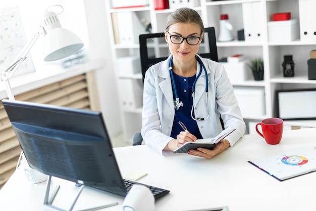 Молодая девушка в белом халате сидит за столом в кабинете и держит в руке ручку и блокнот.