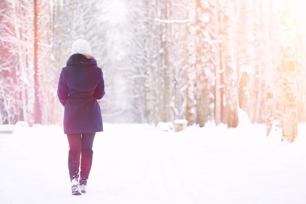 散歩の冬の公園で若い女の子。冬の森のクリスマス休暇。女の子は公園で冬を楽しんでいます。