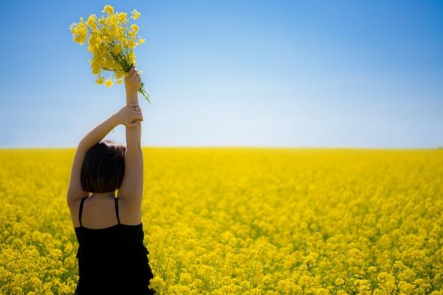 Молодая девушка в желтом поле летом в полдень смотрит вдаль