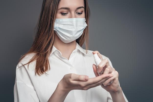Молодая девушка в противовирусной медицинской респираторной маске наносит на руки противовирусный, антисептический спрей для рук на темно-сером