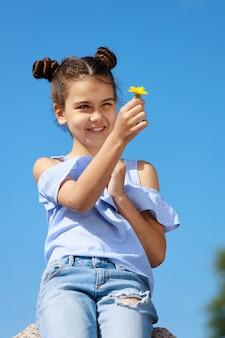 青い服を着た少女は、タンポポを手に持って微笑んで座っています。高品質の写真