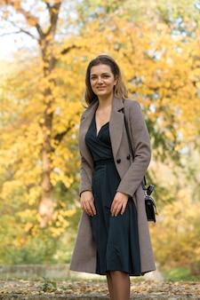 ドレスを着た少女は、黄金色の紅葉を背景に公園でポーズをとる。