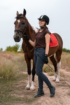 Девушка в костюме для верховой езды кормит свою пегую лошадь, одетую в экипировку для верховой езды.