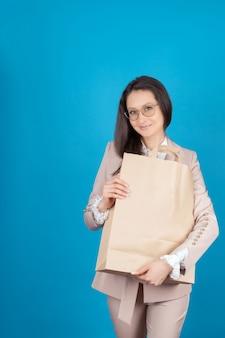 青い背景に眼鏡とビジネス服を着た若い女の子が、手に紙袋を持っている