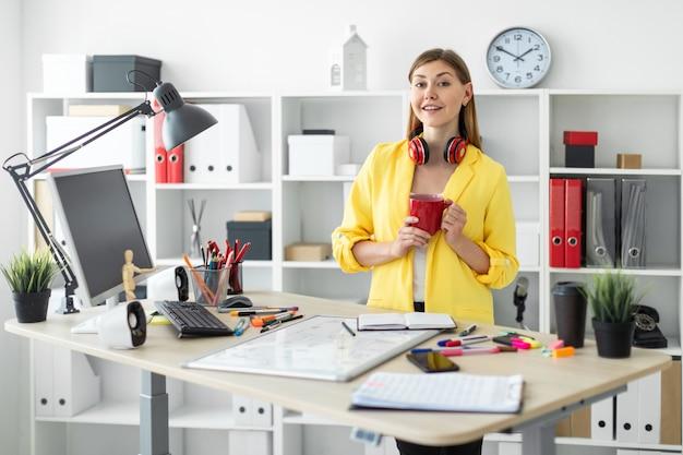 ヘッドフォンの少女は、彼女の手に赤いマグカップを持つテーブルの近くに立っています。テーブルの上の少女が磁気ボードの前に