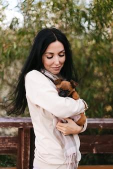 가벼운 옷을 입은 어린 소녀가 어린 강아지를 팔에 안고 있습니다.