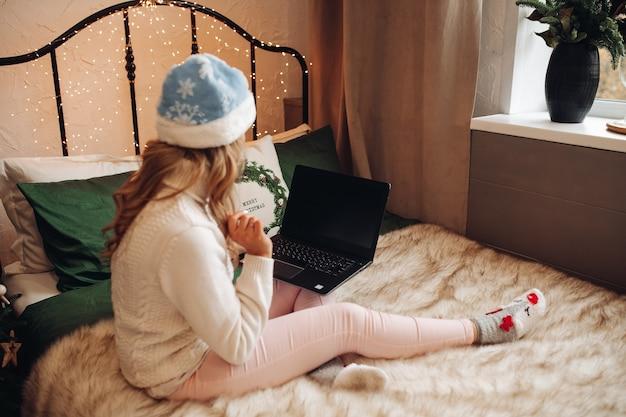 Молодая девушка в новогодней одежде смотрит сериал на кровати