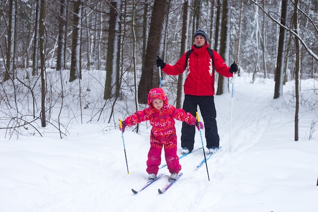 赤いスーツを着た少女がスキーを学んでいます