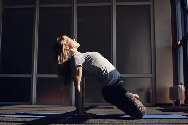 Молодая девушка в спортивной одежде медитирует во время занятий йогой. девушка наклоняется со скрещенными ногами на руках и поворачивает лицо к солнцу. концепция здорового образа жизни. вид сбоку