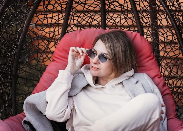 Молодая девушка в солнечных очках отдыхает на природе в кресле