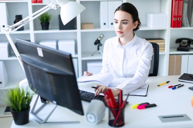オフィスの若い女の子がペンを手に持ち、ドキュメントとコンピューターを操作します。