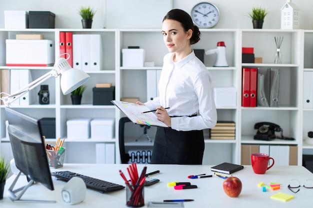 オフィスの若い女の子がテーブルの近くに立って、メモと鉛筆のシートを手に持っています。