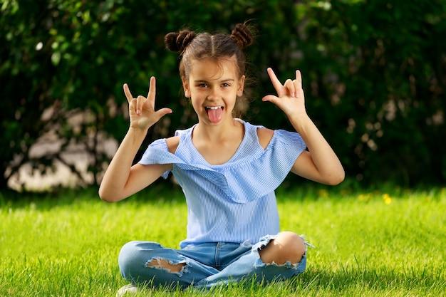 Молодая девушка в парке летом показывает язык. фото высокого качества